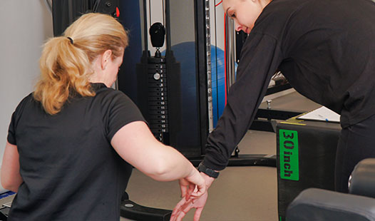 Exercise Physiologist providing a client exercise instruction in the Paramount Physiotherapy gym.