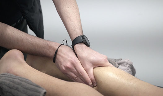 Physiotherapist massaging someone's calf.