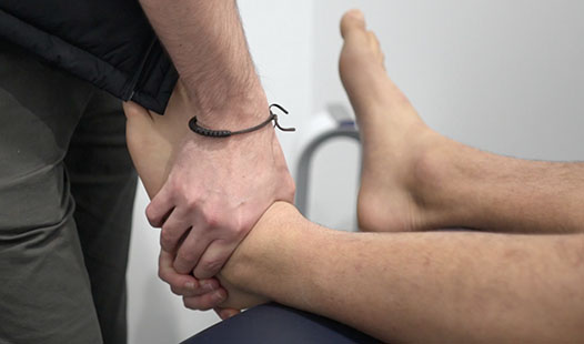 Physiotherapist massaging someone's ankle in the physiotherapy clinic.
