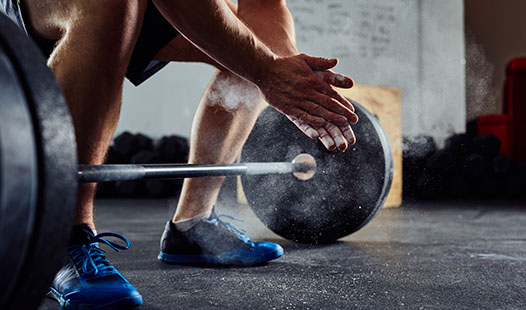 Man in a gym rubbing his hands with chalk getting ready to lift a barbell with weights from the floor.