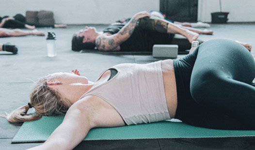 Two women laying on their back on their yoga mats in an exercise class stretching their lower backs and glutes