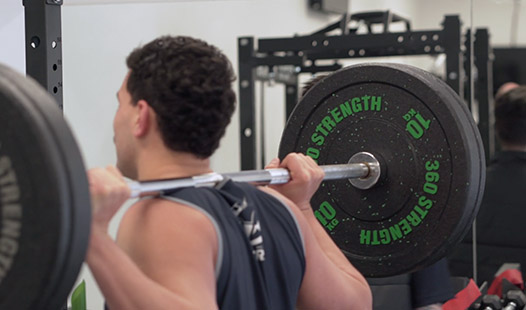 Young athlete in Paramount Physiotherapy Gym with barbell and weights on back, ready to do a squat.