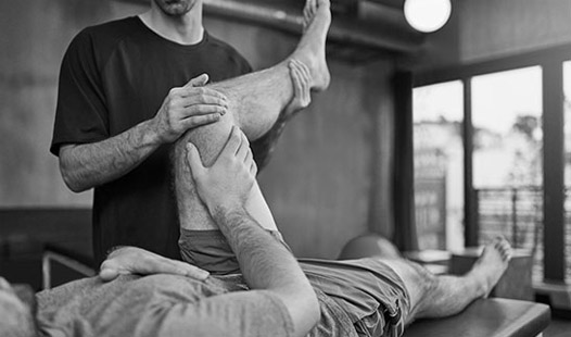 Physiotherapist assessing a mans knee while he is lying on his back.