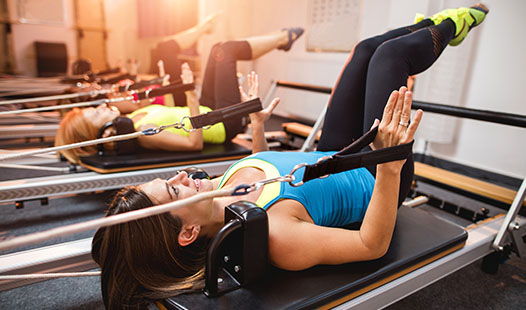Three women in a Pilates studio exercising on Pilates reformers.