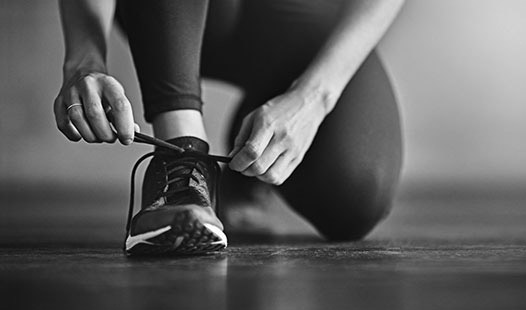 Female exerciser kneeling down and tying her shoes.