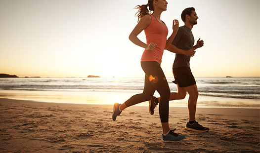 A man and woman running along the beach with a sunset in the background.