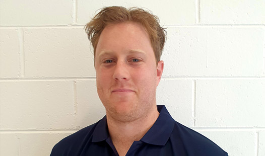 Accredited Exercise Physiologist Bryson Ford's profile picture standing in front of white brick wall.