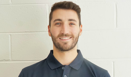 Physiotherapist Dylan Barnaby's profile picture standing in front of white brick wall.
