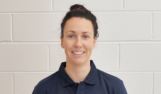 Physiotherapist and Clinical Pilates instructor Sheree Harris's profile picture standing in front of white brick wall.