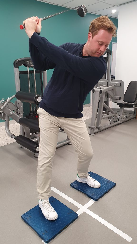 Bryson in the golf back swing with his driver, standing on blue force plates in the Paramount Physiotherapy Gym