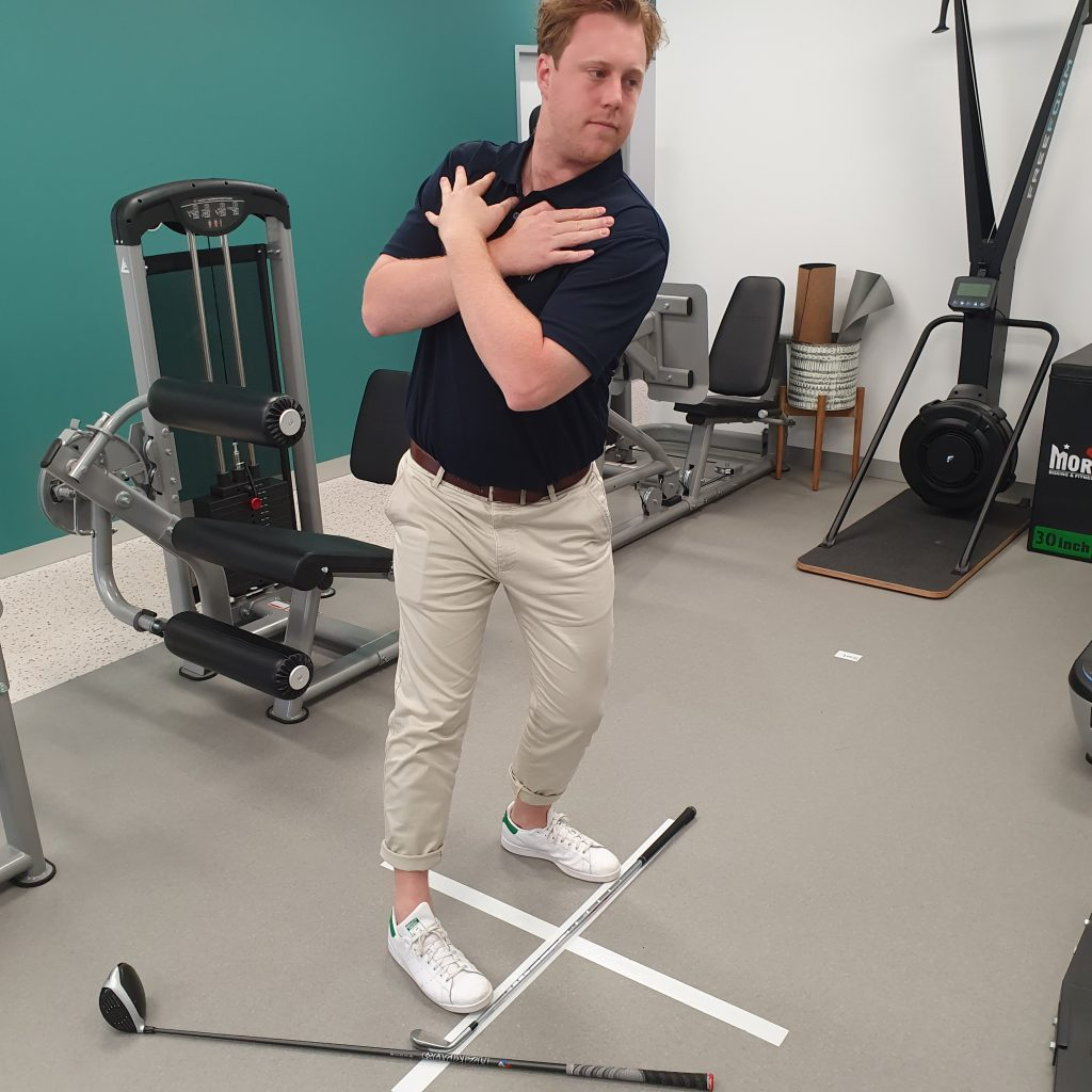 Bryson performing a hip internal rotation in the Paramount Physio Gym for a Golf Assessment.