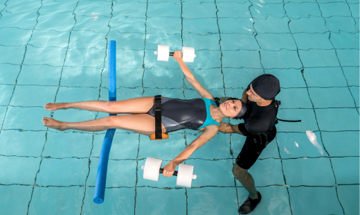 A woman floating on her back with a pool noodle under knees in a hydrotherapy pool, whilst being dragged by Physiotherapist.