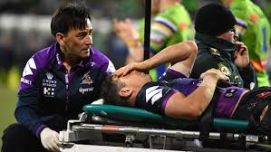 Billy Slater lying on a stretcher holding his head due to concussion with Dr Jason Chan on back on cart