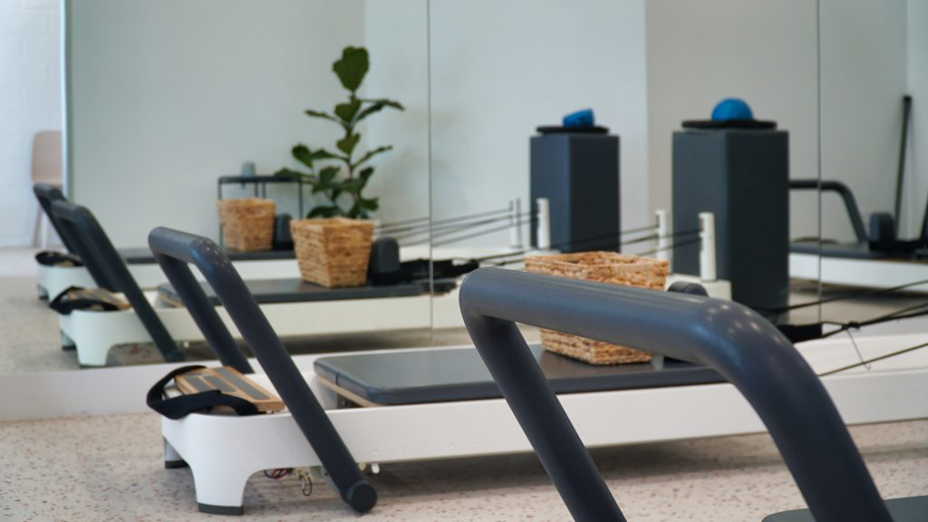 Pilates room with two Allegro 2 reformers and a plant in the background